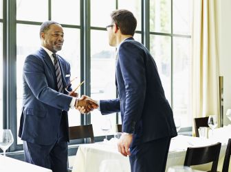 two-businessmen-shaking-hands-at-lunch-meeting-493585563-57717b175f9b585875c2d789