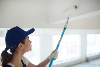 woman-painting-ceiling-with-roller